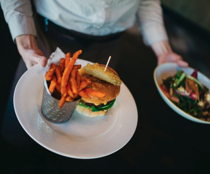 A waiter carrying a salad and a burger with fries