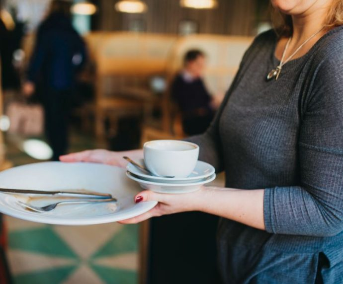 Waitress carrying empty plates