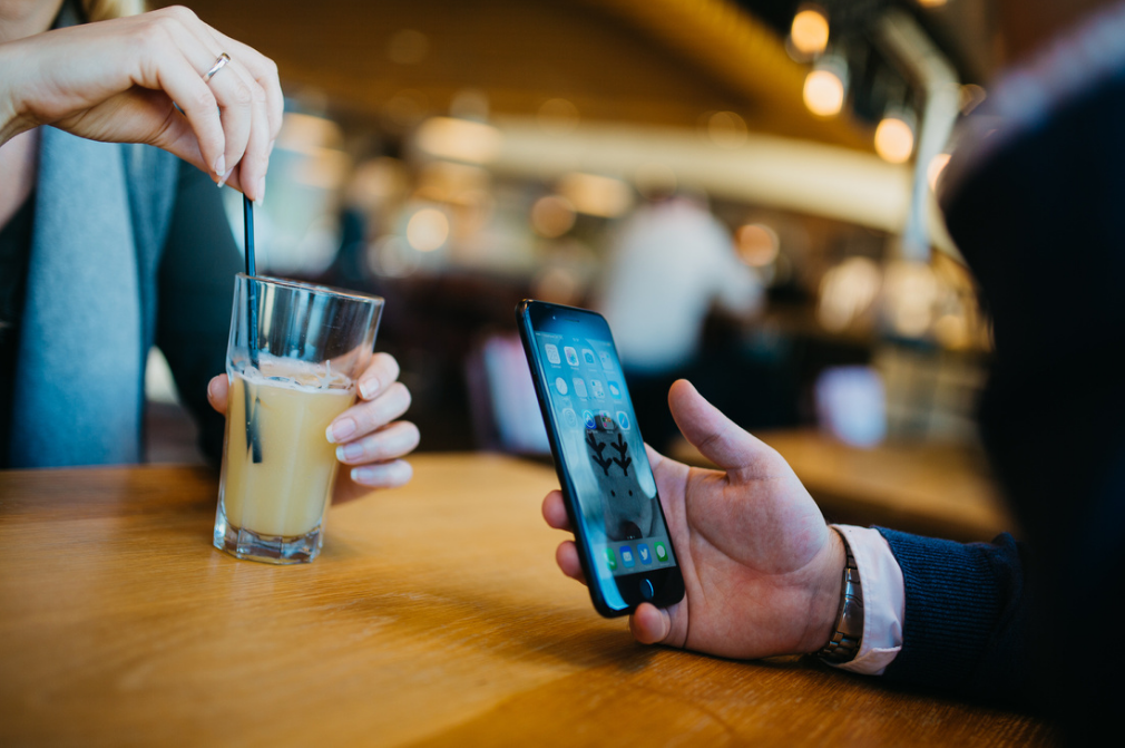 A man sat in a restaurant looking at his mobile telephone sat opposite a woman holding a drink