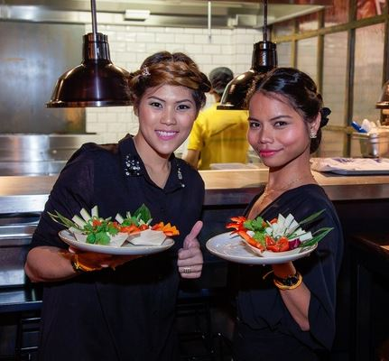 Thai waitresses holding plates of food